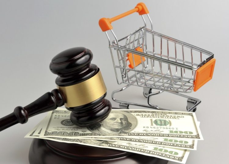 Hammer of judge, pushcart and money on gray background