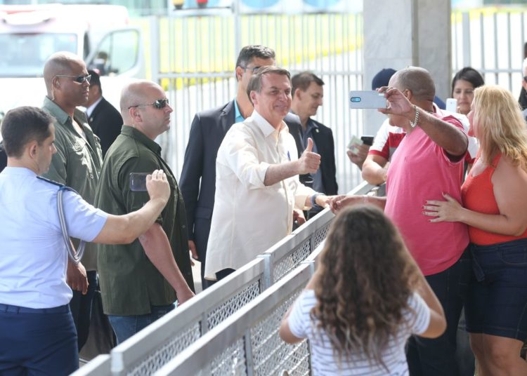 O Presidente Jair Bolsonaro cumprimenta  populares ao sair do Palácio da Alvorada