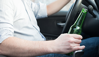 Man driving car and drinking alcohol dangerously