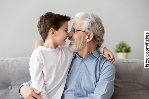 Happy grandfather sit on couch enjoy spending time with preschooler grandson at home, loving smiling grandparent and little boy child relax on sofa have close tender moment touch noses look in eyes