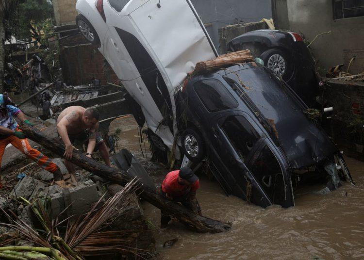 Moradores tentam remover carros danificados de um rio alagado no bairro Realengo após fortes chuvas no Rio de Janeiro, Brasil, 2 de março de 2020. REUTERS / Ricardo Moraes